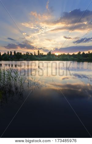 the sunset on the lake on a summer's evening / bright summer photo of the sun's rays Ukraine