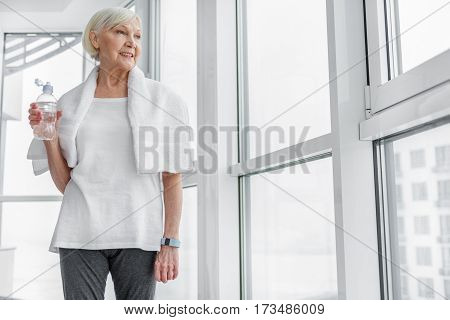 Happy senior woman is drinking water after physical activity. She is standing near window with towel and laughing