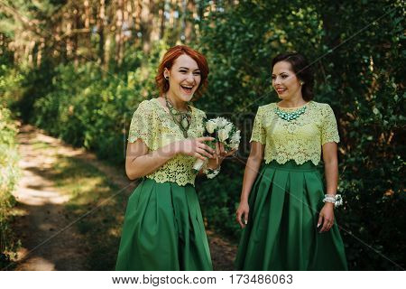 Two gorgeous bridesmaids on green dresses with wedding bouquets on hands.