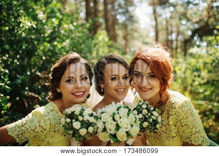 Bride With Bridesmaids With Wedding Bouquet At Hand On Sunny Forest.