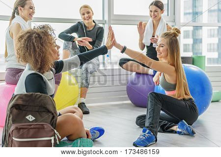 Hilarious smiling young women are sitting on floor near fitness balls. They are clapping hands