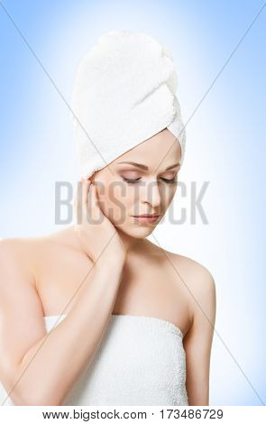 Portrait of young, beautiful woman with bath towel on her head: over blue background. Healthcare, spa, makeup and face lifting concept.