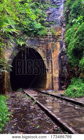 Water cascading across the entrance to an historic abandoned railway tunnel in Helensburg, Sutherland Shire, New South Wales, Australia