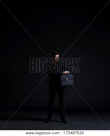 Businessman checking time over black background with copyspace. Money, business and office concept.