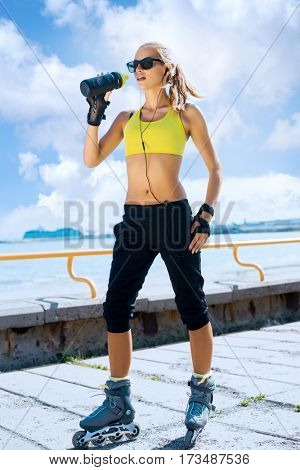 Fit, sporty and athletic young woman. Beautiful girl rollerblading on skates in a sportswear.