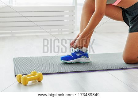 Girl is standing at mat for fitness and tying shoelaces on her blue sneakers. Small yellow dumbbells are near carpet. Close-up