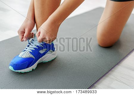 Girl is standing at knee and tying shoelaces on her blue sports shoe. Close up