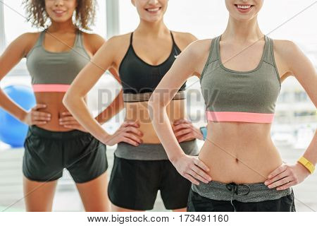Cheerful young women are standing together and doing exercise. They putting hands on waist