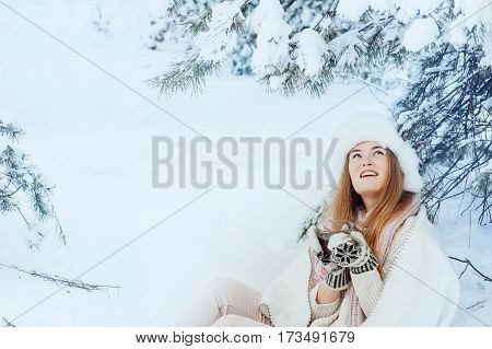 Girl with a cup of tea in his hands sitting in the winter forest