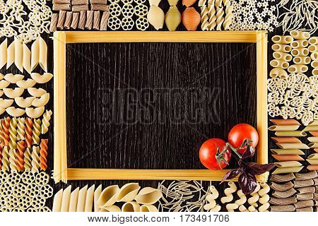 Ingredients Italian pasta on dark brown wooden board with empty copy space as decorative frame background. Mock up restaurant menu.