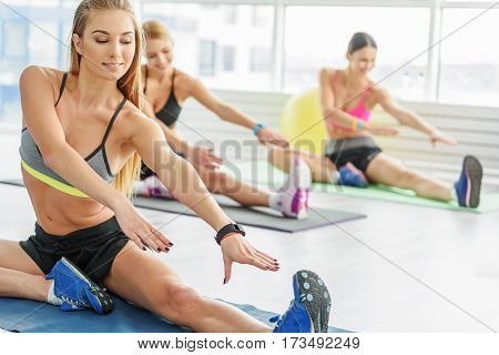 Smiling girls are sitting on sports carpets. They are stretching out to legs