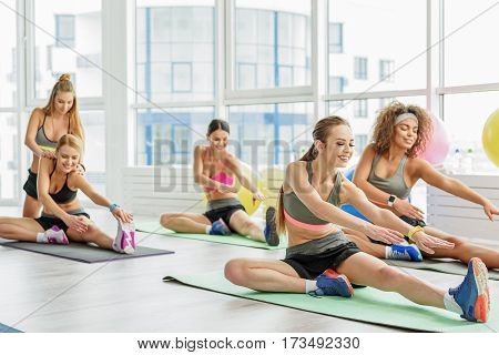 Joyful young women are sitting on sports carpet and gracefully doing necessary gymnastic