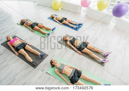 Beautiful young women with slim figures are laying on sports carpets. They smiling with interest