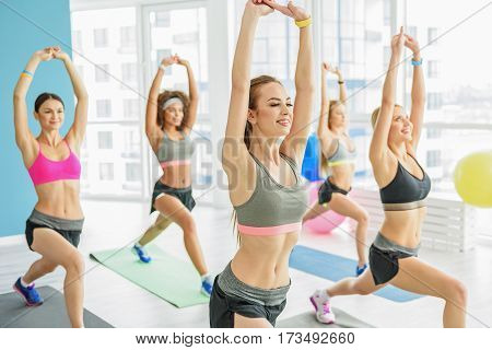 Happy smiling girls are doing special gymnastic in fitness club. They bending one leg at knee and rising hands up