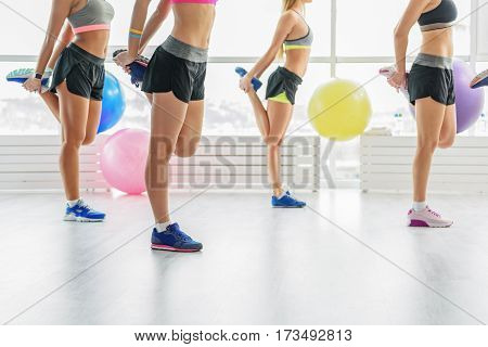 Young women with slim figures are standing on one leg at fitness club