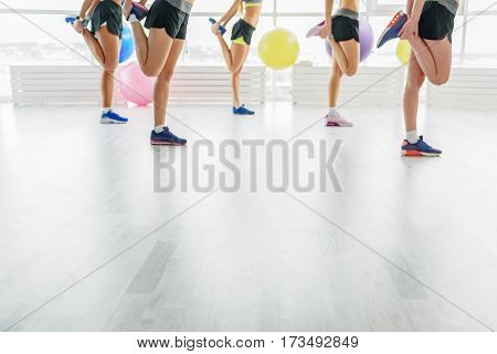 Girls are standing on one leg in light room with big window at gym