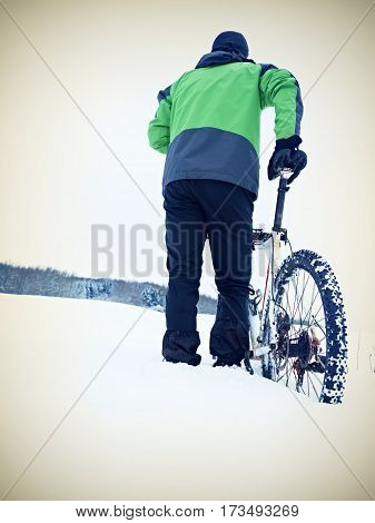 Man With Mountain Bike Stay In Powder Snow.