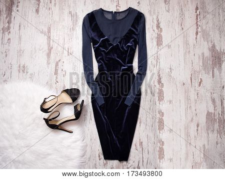 Evening velvet blue dress with chiffon black shoes Wooden background space for text. Fashion concept. top view