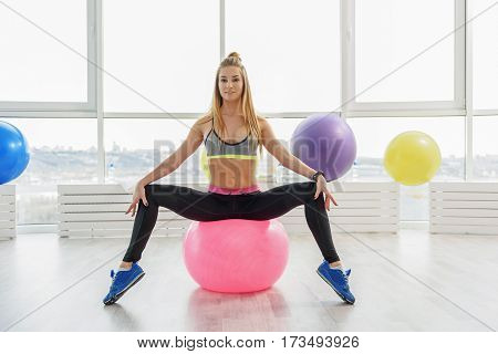 Confident taut girl is sitting on pink convenient ball for fitness. She looking at camera with smile