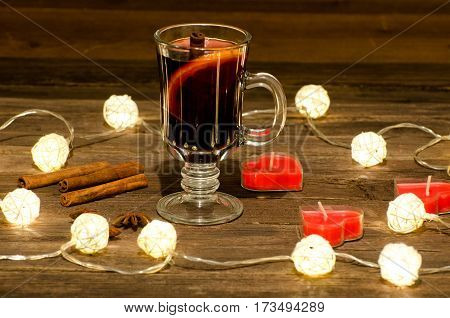 Mug of mulled wine with spices candles in the shape of a heart on a wooden table a garland of lanterns. Cinnamon sticks anise