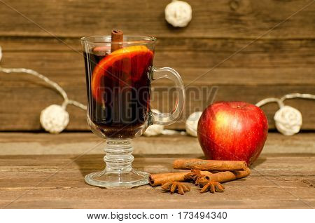 Mug of mulled wine with spices close up. Apple cinnamon sticks and star anise on a wooden table lanterns in the background
