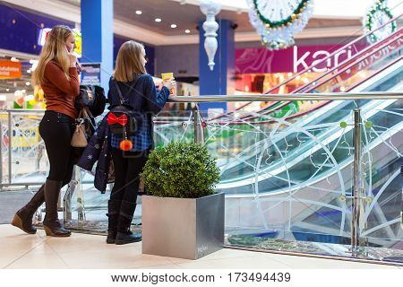 RUSSIA, OREL, MALL GRIN - 21 FEB 2017: Two teenage girls using cellphone inside shopping mall and waiting for somebody