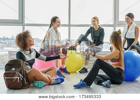 Hilarious girl are sitting together and talking with each other. They looking with laugh