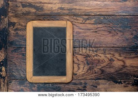 Antique chalkboard on wooden texture. Dark background with copy space for your text. Retro style picture. Top view.