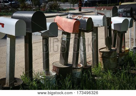 Row of rural mailboxes on wooden posts, anchored in large cement-filled cans.