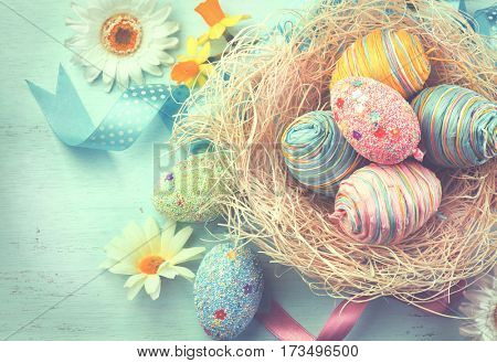 Easter colorful eggs background. Beautiful colorful eggs with decorations over blue wooden background, border design. Vintage style