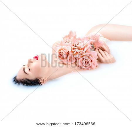 Spa beauty model girl taking milk bath, spa and skin care concept. Beauty young Woman with bright makeup and pink rose flower relaxing in milk bath. Rejuvenation