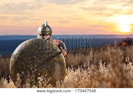 Ancient Greek soldier holding a sword hiding behind his shield on the battlefield ready to attack copyspace. Spartan warrior on the battlefield beautiful sunset on the background bravery hero concept