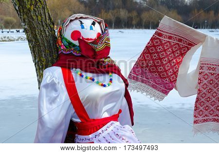 Shrovetide doll in colorful headscarf and sarafan near tree on background of spring landscape