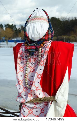 Shrovetide doll in colorful folk costume outdoors