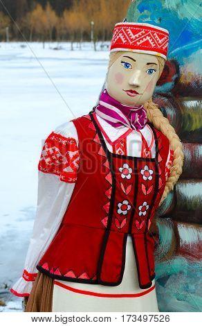 Shrovetide doll in bright folk costume on open air