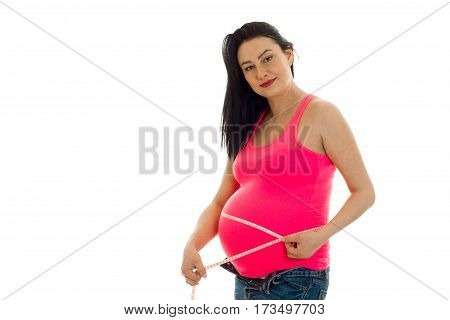 portrait of pregnant young brunette in pink shirt measure her belly with tape and posing on camera isolated on white