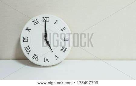 Closeup white clock for decorate show 5 o'clock on white wood desk and cream wallpaper textured background with copy space