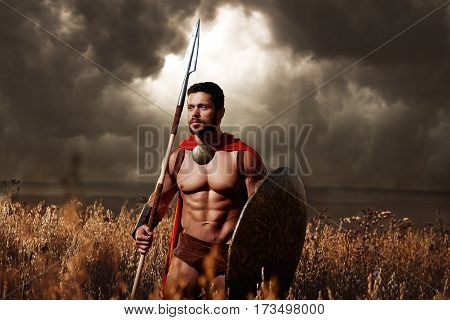 Pure masculinity. Sepia toned shot of a young athletic Greek warrior standing in the field armed with a spear and a shield posing under gloomy skies looking away thoughtfully trustworthy confidence