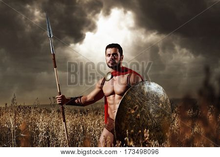 He knows no fear. Sepia toned shot of a Spartan warrior with strong muscular torso wearing red cape holding a spear and a shield walking through the field alone dramatic gloomy sky on the background