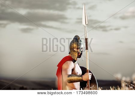 Empire warrior. Ancient shirtless warrior with perfect strong muscular body wearing a helmet and a cape standing in the field with a shield and a spear under grey sky copyspace confidence concept