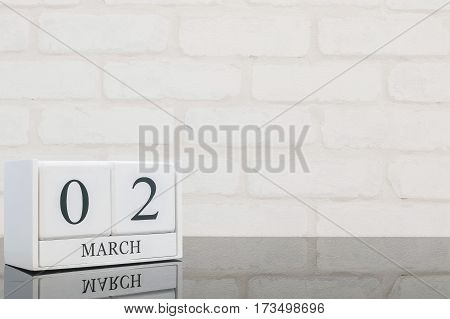 Closeup white wooden calendar with black 2 march word on black glass table and white brick wall textured background with copy space selective focus at the calendar