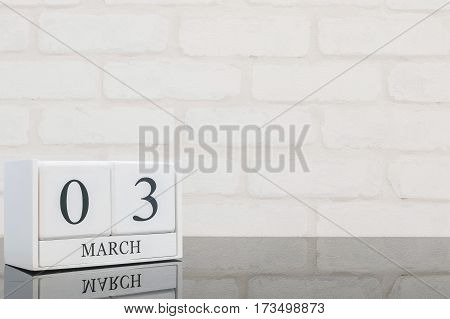 Closeup white wooden calendar with black 3 march word on black glass table and white brick wall textured background with copy space selective focus at the calendar