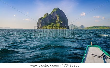 Banca Boat approaching Huge Rocky Island on Windy Day, El, Nido, Palawan, Philippines