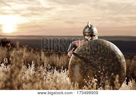Fearless Roman army soldier attacking with his sword protecting himself with a shield. Medieval warrior wearing a helmet armed with a sword and covering himself with a shield sunset on the background