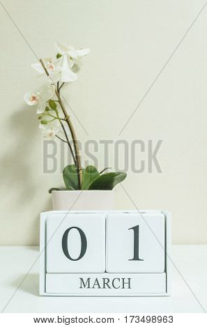 Closeup white wooden calendar with black 1 march word with white orchid flower on white wood desk and cream color wallpaper in room textured background selective focus at the calendar