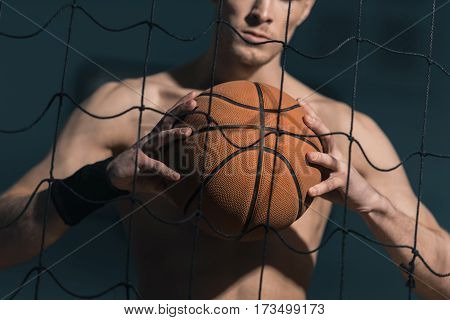 partial view of sporty man holding basketball ball in hands