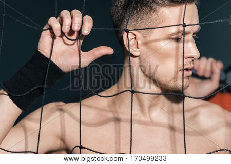 portrait of pensive sporty man standing near net