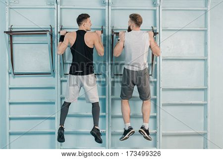 back view of sporty men exercising on sport equipment in gym