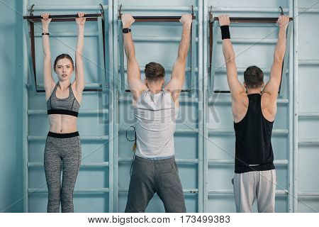 sporty men and woman hanging on sport equipment in gym