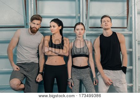 confident sporty men and women in gym